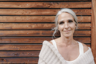 Portrait of smiling mature woman in front of wooden facade - KNSF03471