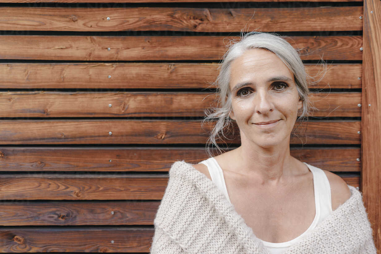 Portrait of smiling mature woman in front of wooden facade - KNSF03471 - Kniel Synnatzschke/Westend61