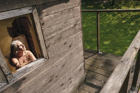 Woman in tree house enjoying sunlight - KNSF03480