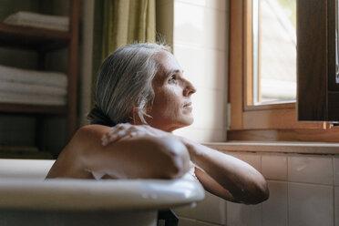 Portrait of pensive woman in bathtub looking out of window - KNSF03483