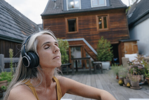 Portrait of mature woman listening music with headphones on terrace - KNSF03495