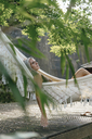 Pensive woman relaxing in hammock in the garden - KNSF03504