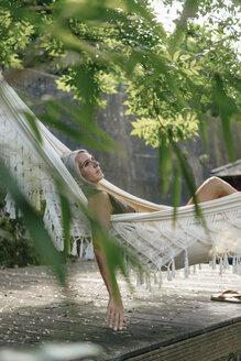 Pensive woman relaxing in hammock in the garden - KNSF03504