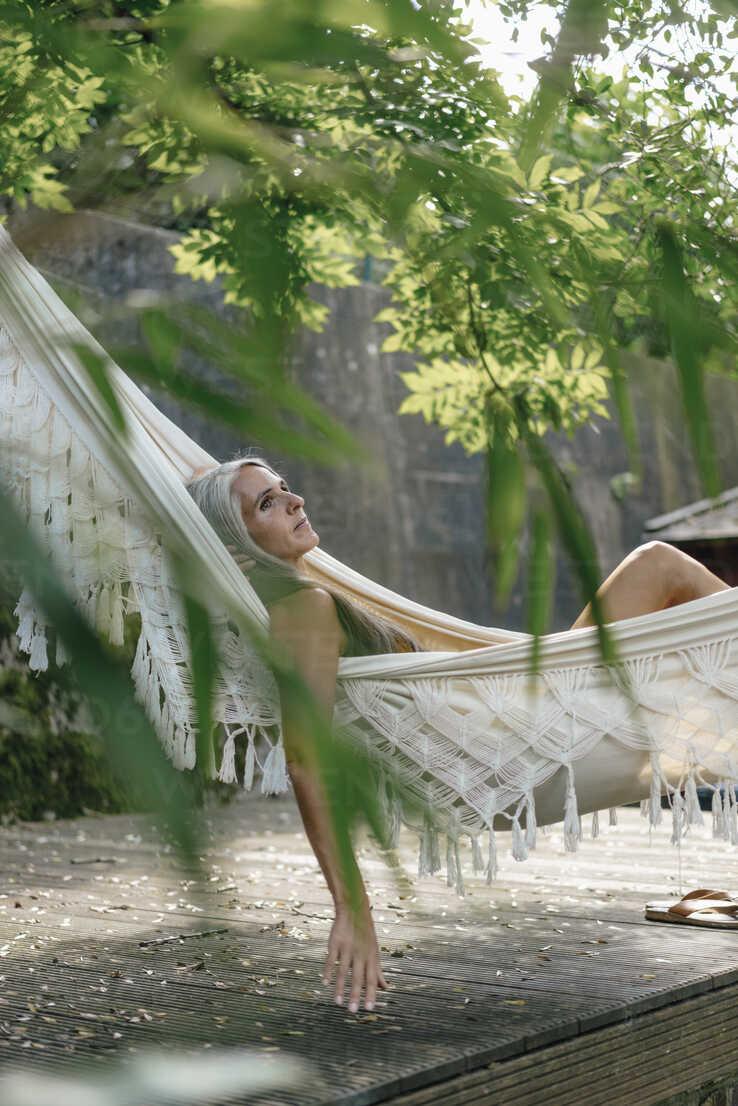 Pensive woman relaxing in hammock in the garden - KNSF03504 - Kniel Synnatzschke/Westend61
