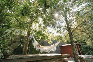 Woman relaxing in hammock in the garden - KNSF03507