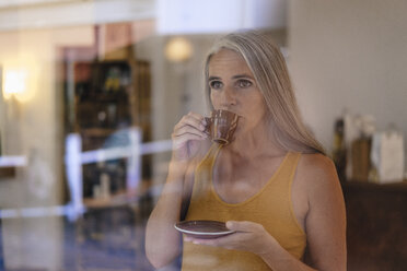 Portrait of businesswoman drinking cup of coffee in her shop - KNSF03522