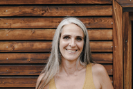Portrait of smiling mature woman in front of wooden facade - KNSF03525