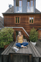 Woman relaxing on garden table at the backyard of her house - KNSF03531