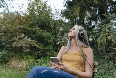 Woman with cell phone sitting in the garden listening music with headphones - KNSF03540