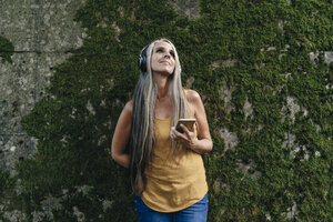 Woman with cell phone standing in front of wall listening music with headphones - KNSF03543