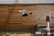 Gymnast exercising at vaulting table in gym - OCAF00011