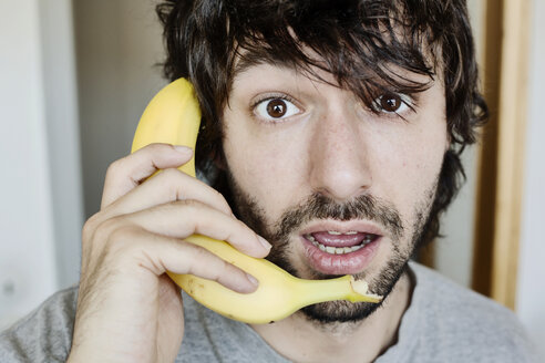 Portrait of astonished young man telephoning with banana - JATF00977