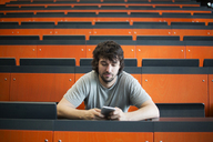 Portrait of student in auditorium at university looking at cell phone - JATF00980