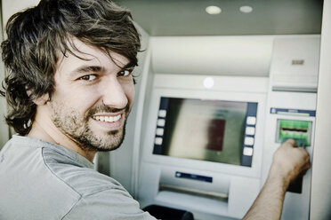 Portrait of laughing young man using cash machine - JATF00986