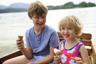 Portrait of little girl sitting in rowing boat with her brother eating icecream - ECPF00145