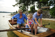 Germany, Bavaria, Murnau, grandfather with grandson and granddaughter in rowing boat - ECPF00148
