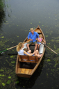 Family relaxing in rowing boat on lake - ECPF00157