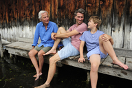Boy sitting with grandfather and father together on jetty in summer - ECPF00169