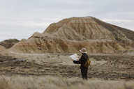 Woman with map standing in barren landscape - JPF00302