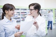 Pharmacist talking to woman with paper in pharmacy - WESTF23913