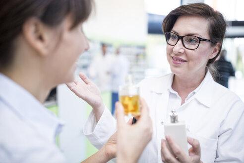 Pharmacist advising customer in pharmacy - WESTF23916