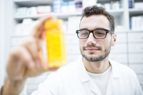 Smiling pharmacist holding pill box in pharmacy - WESTF23928