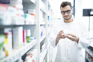 Pharmacist holding product at shelf in pharmacy - WESTF23934
