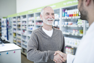Pharmacist and customer shaking hands in pharmacy - WESTF23937