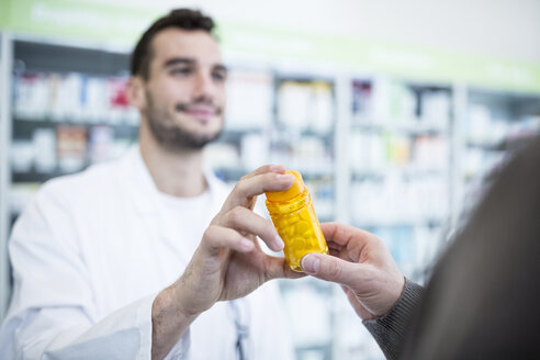 Close-up of harmacist giving pill box to customer in pharmacy - WESTF23940