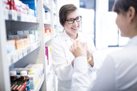 Pharmacist advising customer in pharmacy - WESTF23946