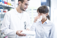 Pharmacist advising customer in pharmacy - WESTF23949