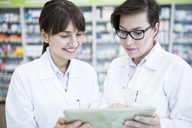Two pharmacists using tablet in pharmacy - WESTF23952