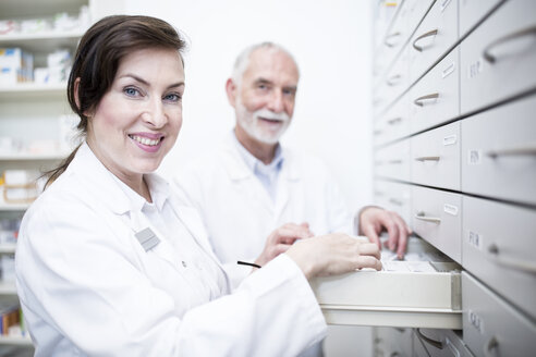 Portrait of two smiling pharmacists at cabinet in pharmacy - WESTF23958