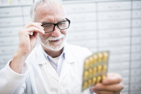 Smiling pharmacist holding tablet package in pharmacy - WESTF23961