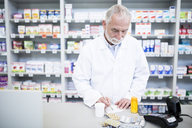 Pharmacist with medicine at counter in pharmacy - WESTF23964