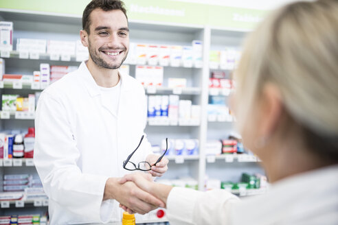 Pharmacist and customer shaking hands in pharmacy - WESTF23967