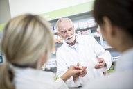 Pharmacist with two women in pharmacy - WESTF23973