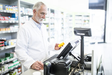 Pharmacist with medicine at counter in pharmacy - WESTF23976