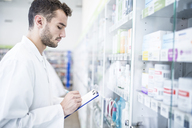 Pharmacist holding clipboard at shelf in pharmacy - WESTF23979