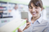Smiling woman in pharmacy holding smartphone and medicine - WESTF23982