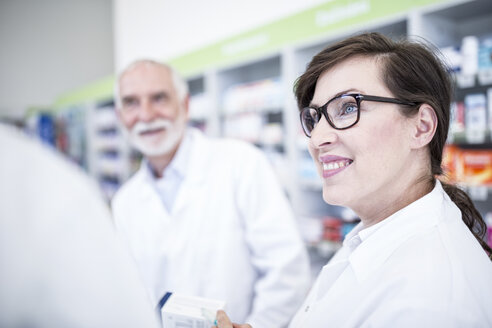 Smiling pharmacist with colleague in pharmacy - WESTF23985