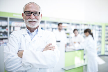 Portrait of smiling pharmacist in pharmacy with colleagues in background - WESTF23988