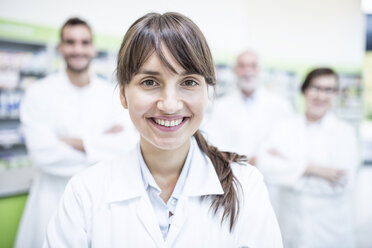 Portrait of smiling pharmacist in pharmacy with colleagues in background - WESTF23991