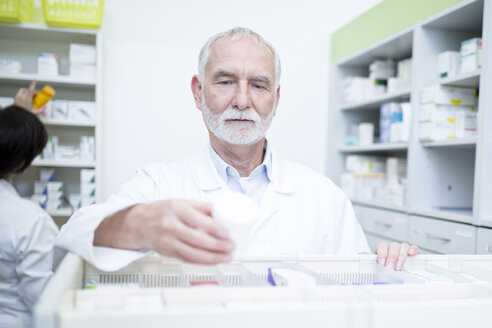 Pharmacist taking medicine from cabinet in pharmacy - WESTF23994