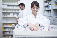 Smiling pharmacist seeking out medicine at cabinet in pharmacy - WESTF23997