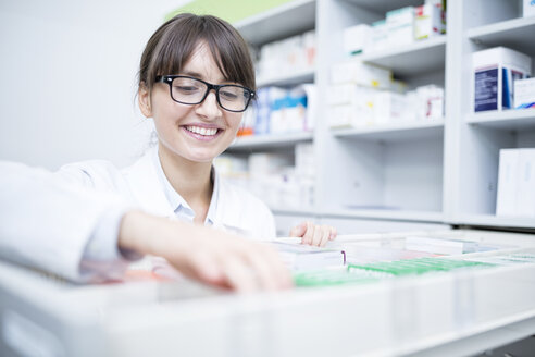 Smiling pharmacist seeking out medicine at cabinet in pharmacy - WESTF24000