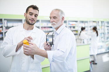 Two pharmacists examining medicine in pharmacy - WESTF24003