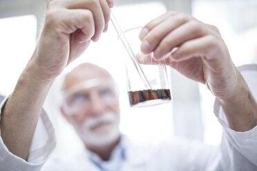 Man holding beaker in laboratory - WESTF24015