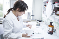 Woman preparing medicine in laboratory of a pharmacy - WESTF24024