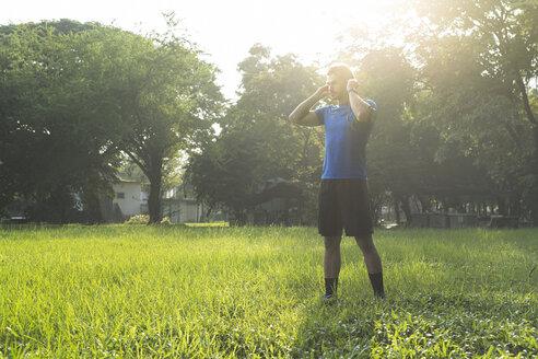 Runner standing in urban park, wearing headphones - SBOF01109